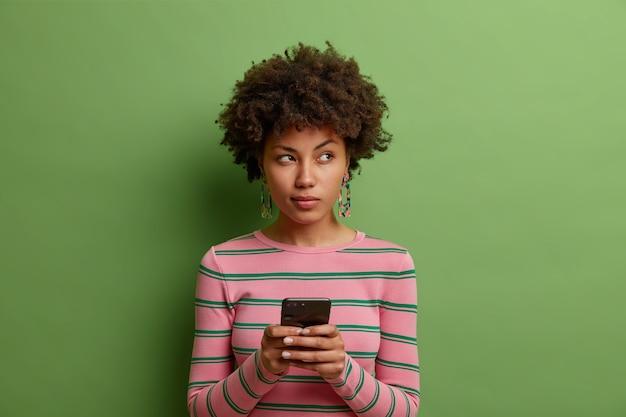 Mulher afro-americana pensativa usa aplicativo de namoro em smartphone olhando para o outro lado e usa um suéter casual isolado sobre uma parede verde