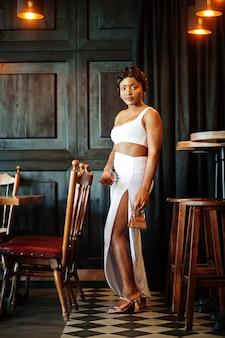 Mulher afro-americana, penteado retrô em vestido branco no restaurante.