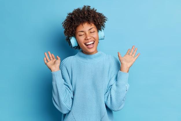 Mulher afro-americana positiva com cabelo encaracolado levanta as palmas das mãos e se diverte enquanto ouve uma trilha de áudio usa fones de ouvido sem fio vestindo um macacão casual