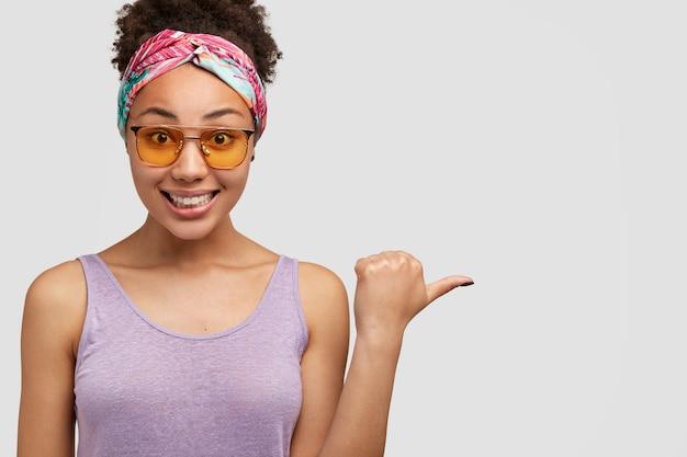 Mulher afro-americana positiva com sorriso gentil apontando para copyspace