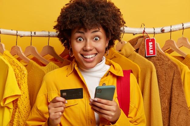Mulher afro-americana positiva e surpresa com um sorriso amplo, usa smartphone moderno e cartão de crédito