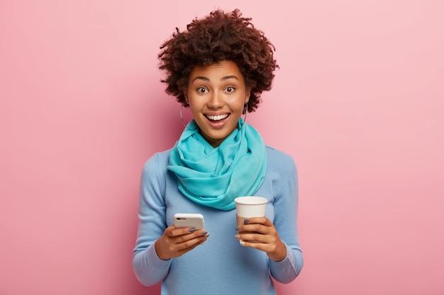Mulher afro-americana positiva envia mensagens de texto via smartphone, bebe café para viagem, aproveita o tempo livre, usa um macacão casual azul com lenço de seda, sorri positivamente