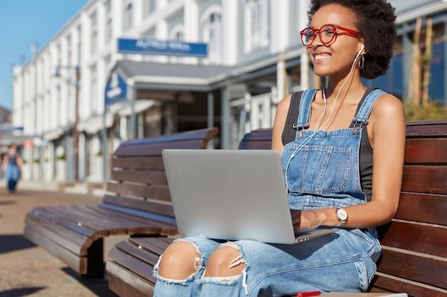 Mulher afro-americana positiva ouve música com fones de ouvido e trabalha em um laptop, vestida de macacão jeans, sorri positivamente, senta-se em um banco contra o ambiente urbano, focada na distância