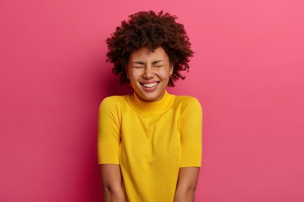 Mulher afro-americana positiva sorri feliz, ri de uma piada engraçada, veste roupas amarelas, fecha os olhos com prazer, isolada sobre a parede rosa. conceito de pessoas, emoções e expressões faciais