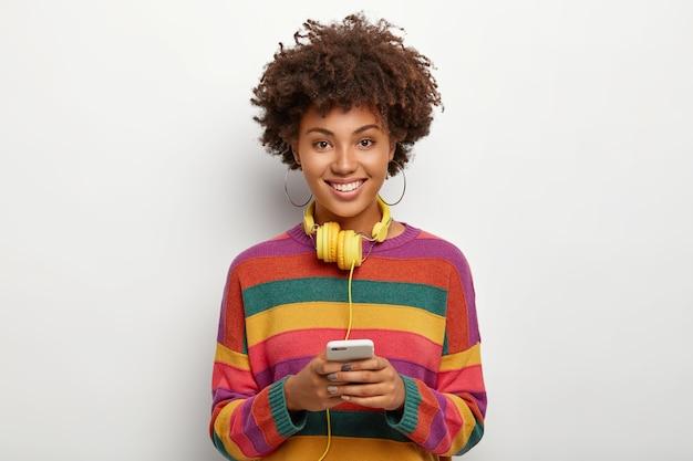 Mulher afro-americana positivamente encantada, vestida com um suéter listrado colorido, segura um celular moderno conectado a fones de ouvido, navega na internet