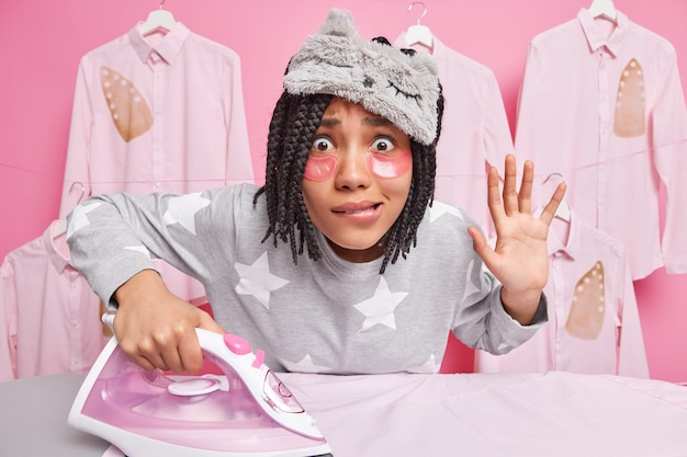 Mulher afro-americana preocupada com dreadlocks morde lábios mantém a palma da mão levantada olha atentamente para movimentos de câmera roupas usa ferro elétrico usa pijama macio com máscara de dormir
