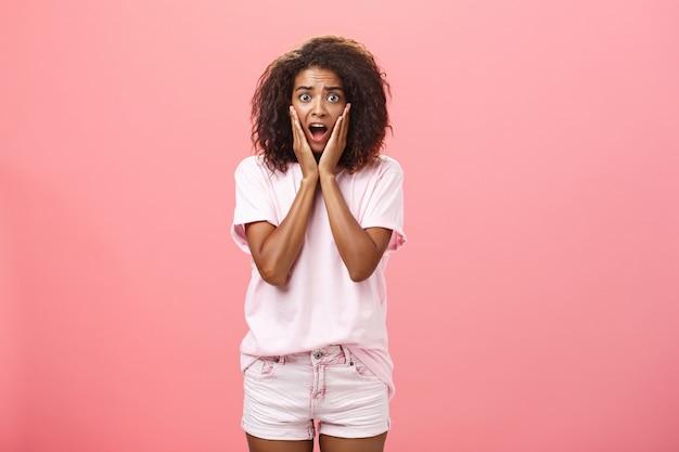 Mulher afro-americana preocupada com penteado encaracolado em roupa da moda, com a boca aberta, de mãos dadas no rosto.