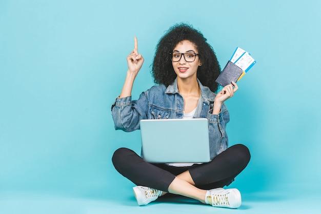 Mulher afro-americana preta feliz consideravelmente nova que senta-se no assoalho com os bilhetes do portátil e de avião isolados sobre o fundo azul. apontando o dedo para cima.