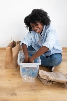 Mulher afro-americana reciclando para um ambiente melhor