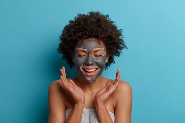 Mulher afro-americana relaxada positiva ri alegremente com os olhos fechados, aplica máscara de beleza para rejuvenescimento, mantém as palmas das mãos para o lado, mostra os ombros nus, pele saudável e macia, isolada na parede azul