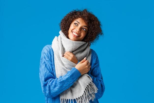 Mulher afro-americana romântica e despreocupada com um suéter de inverno, lenço, olhando para cima, pensativa, parede azul