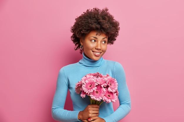 Mulher afro-americana romântica satisfeita segurando um buquê de gérberas e recebendo flores