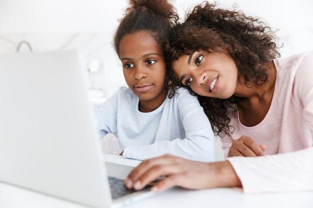 Mulher afro-americana satisfeita e sua filha usando o laptop em casa