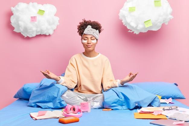 Mulher afro-americana satisfeita medita na cama, sente-se relaxada, usa pijamas, fecha os olhos, pratica ioga depois de estudar, bebe café