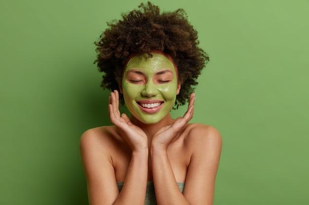 Mulher afro-americana satisfeita toca o rosto suavemente aplica máscara nutritiva verde sorri suavemente fica com os ombros nus no interior sente-se revigorada após o banho