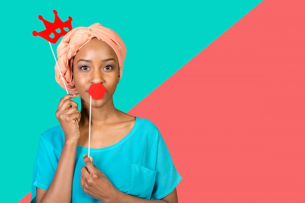 Mulher afro-americana se divertindo com adereços de foto