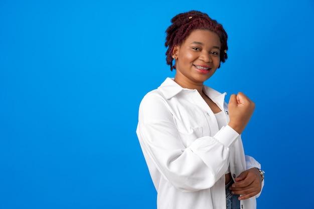Mulher afro-americana se sentindo forte, mostrando o punho contra um fundo azul