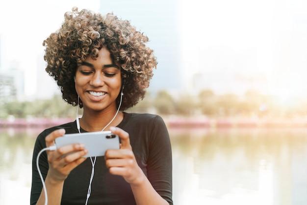 Mulher afro-americana segurando smartphone na mídia remixada da natureza