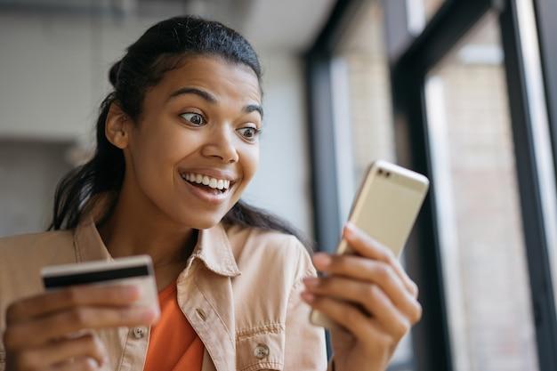 Mulher afro-americana, segurando um cartão de crédito, usando o smartphone, fazendo compras online. freelancer emocional recebe pagamento