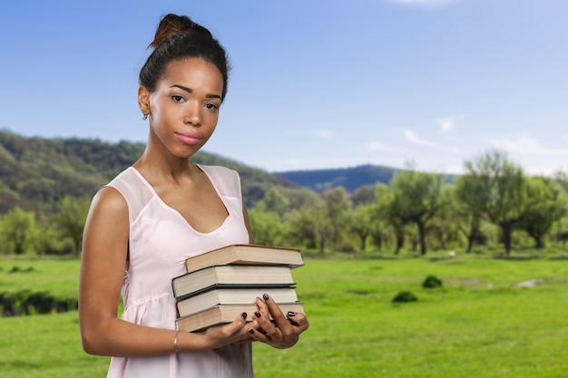 Mulher afro-americana, segurando uma pilha de livros