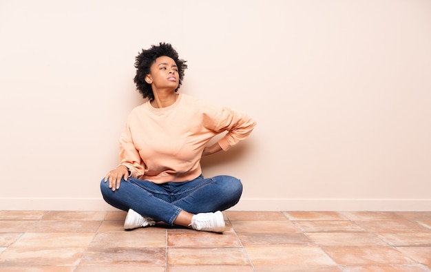 Mulher afro-americana sentada no chão