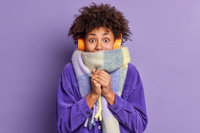 Mulher afro-americana sente muito frio durante o tempo gelado usa jaqueta roxa e lenço quente em volta do pescoço wals na rua durante o inverno ouve música através de fones de ouvido sem fio mantém as mãos juntas