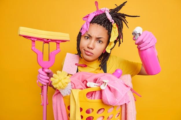Mulher afro-americana séria, cuidando da limpeza, segura o detergente e o esfregão olha com atenção