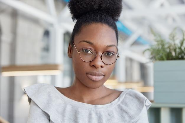 Mulher afro-americana séria, de pele muito escura, com lábios carnudos, usa óculos redondos, posa em ambientes internos e senta-se em um escritório espaçoso