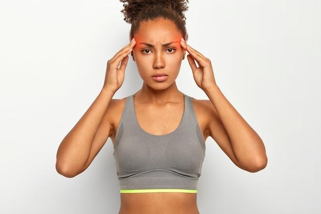 Mulher afro-americana séria e tensa sofre de dores terríveis nas têmporas, enxaqueca, fica exausta após um longo treinamento físico, usa top, posa contra a parede branca do estúdio