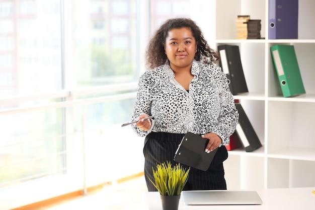 Mulher afro-americana séria em camisa no escritório.