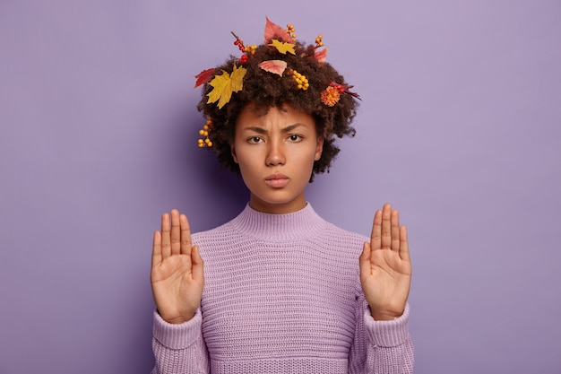 Mulher afro-americana séria franze a testa e mostra o gesto de pare, usa um suéter tricotado quente, mantém as palmas das mãos estendidas para a câmera, tem folhas de outono presas no cabelo encaracolado. estação, linguagem corporal