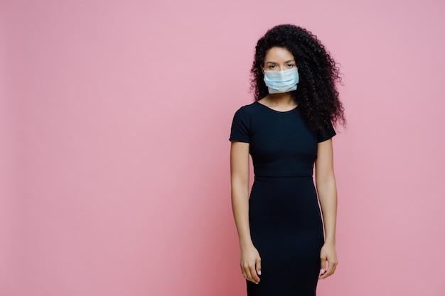 Mulher afro-americana séria usa máscara médica descartável no rosto