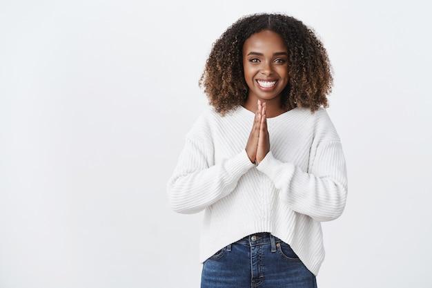 Mulher afro-americana simpática e encantadora, sorridente, pressiona as palmas das mãos em súplica, reza o gesto pedindo ajuda, sorrindo agradecida emprestar dinheiro parede branca