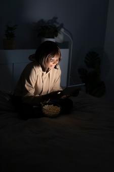Mulher afro-americana sorridente assistindo netflix em casa