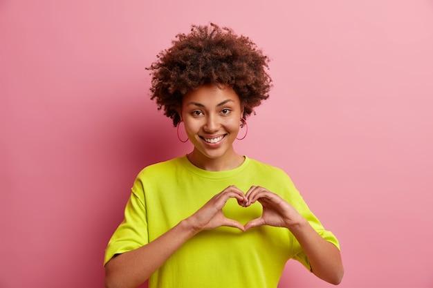 Mulher afro-americana sorridente e fofa faz gesto de eu te amo, confessa que está apaixonada, expressa simpatia, mostra sinal de coração vestida com roupas casuais, isolada sobre a parede rosa