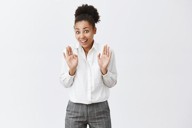 Mulher afro-americana sorridente, levantando as mãos em sinal de rendição, pare algo