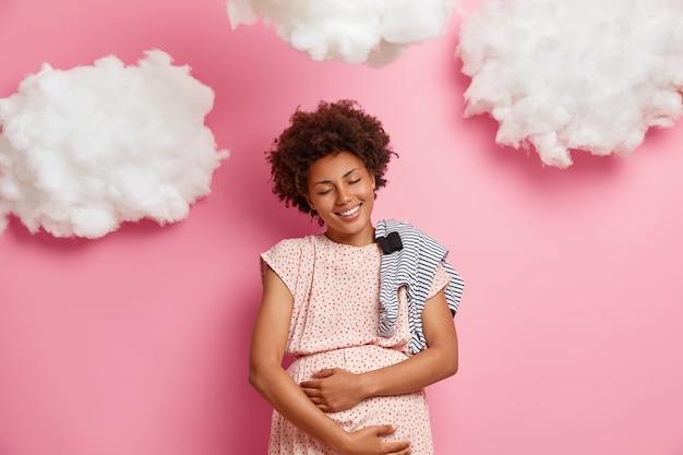 Mulher afro-americana sorridente muito feliz toca suavemente a barriga e apalpa o bebê, compra macacão para recém-nascido, aproveita o momento da maternidade e da maternidade, brinca com o precioso futuro filho por nascer