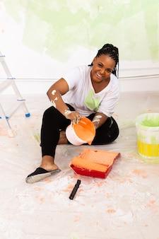 Mulher afro-americana sorridente, pintando a parede interior da casa. renovação, reparo e redecoração