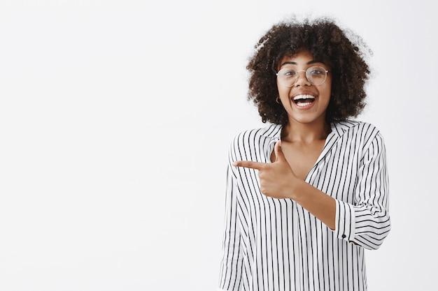 Mulher afro-americana superemotiva, animada e feliz, de blusa listrada e óculos, rindo da diversão e da alegria, apontando para a esquerda com o dedo indicador, divertindo-se muito sobre a parede cinza