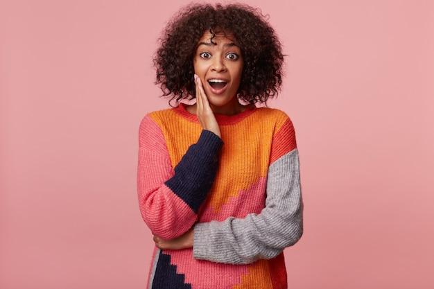 Mulher afro-americana surpresa com um penteado afro com aparência de espanto, a palma da mão segura sua bochecha, sente-se impressionada, parece afetada, excitada, exagerada, isolada