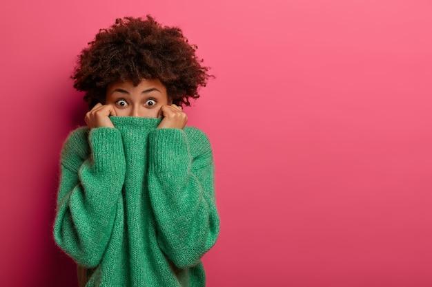 Mulher afro-americana surpresa positiva esconde rosto com suéter, brinca e parece animada