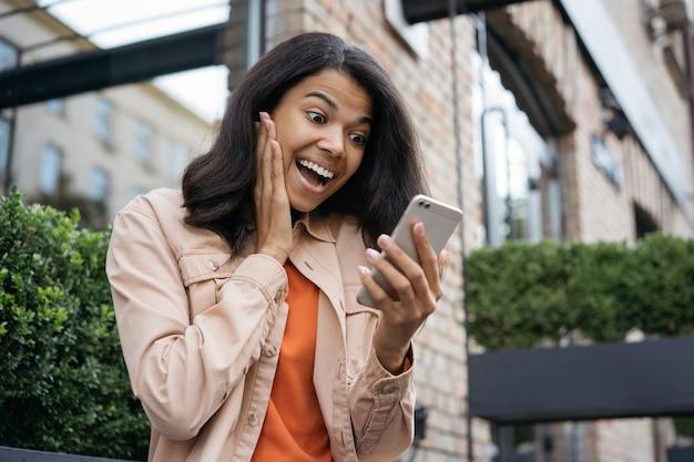 Mulher afro-americana surpresa usando telefone celular, olhando para a tela digital, ganhando na loteria online, comemorando o sucesso