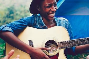 Mulher afro-americana, tocando uma guitarra em um parque de campismo