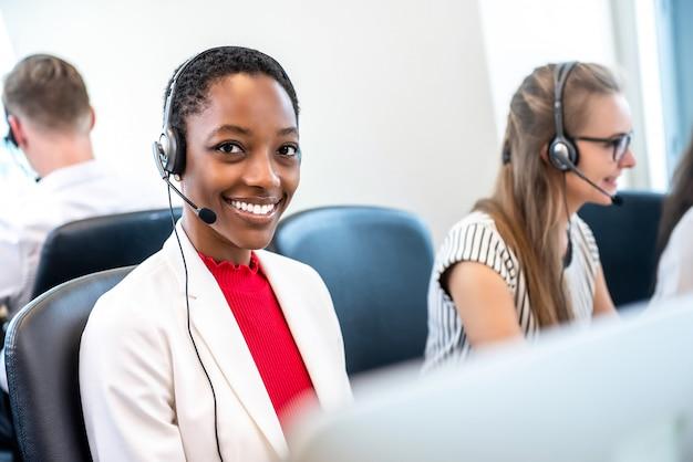 Mulher afro-americana, trabalhando no escritório do centro de chamada com equipe diversificada