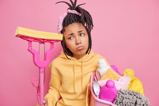 Mulher afro-americana triste e insatisfeita sente cansaço depois de fazer o trabalho doméstico e usa ferramentas de limpeza