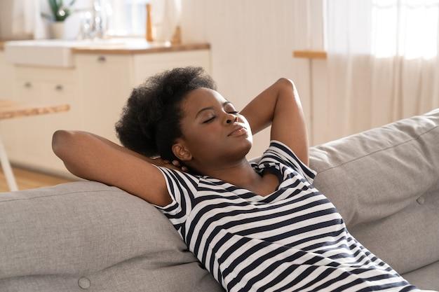 Mulher afro-americana usa camiseta listrada dormindo no sofá com o braço sob a cabeça em casa. resto.