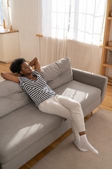 Mulher afro-americana usa uma camiseta listrada relaxando no sofá com o braço sob a cabeça em casa. dia de preguiça