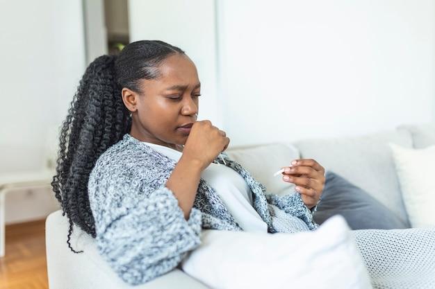 Mulher afro-americana usando cotonete ao fazer teste de pcr para coronavírus em casa. mulher usando teste diagnóstico rápido de coronavírus. mulher jovem em casa usando um cotonete nasal para covid-19.