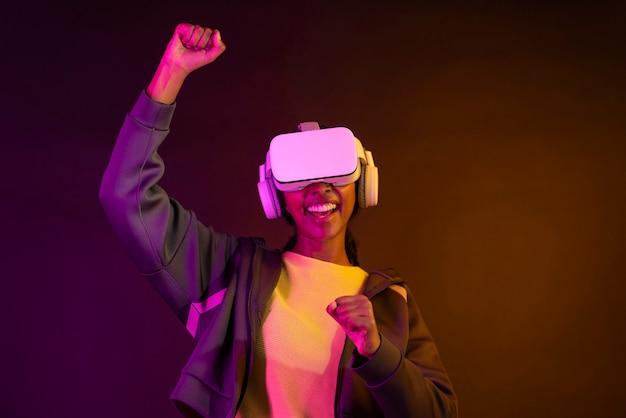 Mulher afro-americana usando gadget de realidade virtual para se divertir