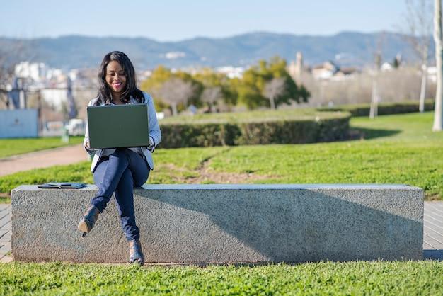 Mulher afro-americana usando um laptop em um parque ao ar livre